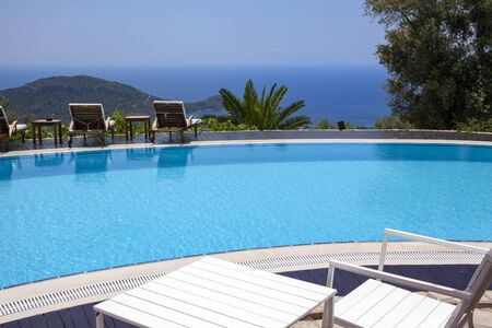 Swimming pool in the garden and beautiful mountain and sea landscape with trees and sunbeds.