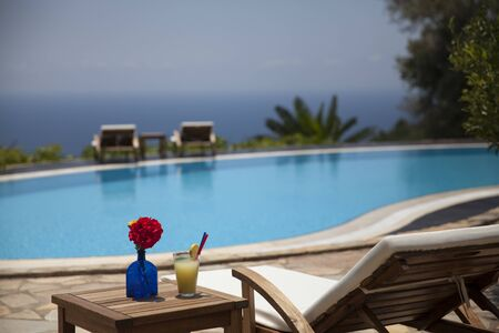 Fresh summer cocktail and sunbed. Swimming pool with mediterranean background. Stok Fotoğraf