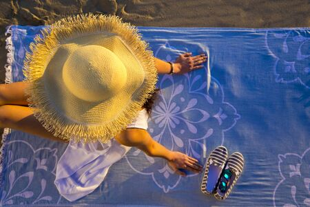 top view of a woman wearing white stylish summer hat and sitting on a cover on the beach, sitting and relaxing, sunbathing.