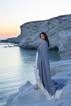 peaceful brunette woman watching the sea and beautiful sunset, covered herself with a blanket. Stok Fotoğraf