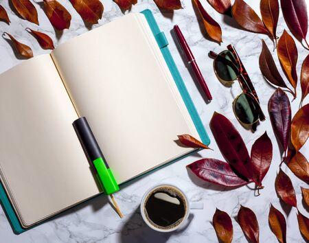 notebook and pen on marble floor with faded leaves, coffee and sunglasses. study table. Reklamní fotografie
