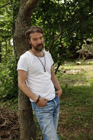 Handsome man leaning on a tree in a natural parkland. Bearded man in his 40's looking at camera with a smiling face, wearing white T-shirt and denim jeans Standard-Bild