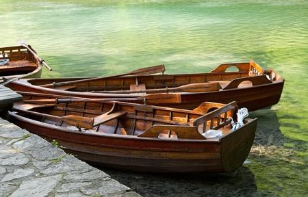 rowboats: Rowboats moored on green lake.