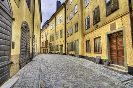 Old cobblestone street with yellow houses.