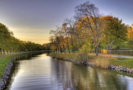 waterway: Idyllic treelined canal in autumn. Stock Photo