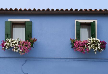 Decorative windows with flowers on a blue building. Stock Photo