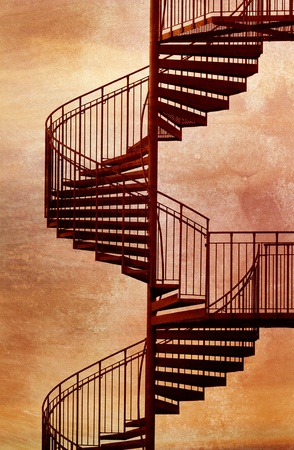 Red metal spiral staircase with grungy background. Stock Photo