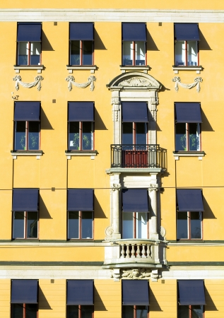 awnings: Old yellow facade with blue awnings