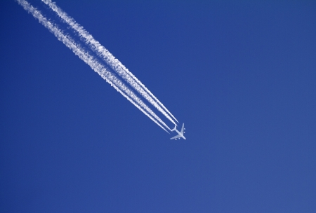 Airplane with condensation trails on blue sky  Stock Photo