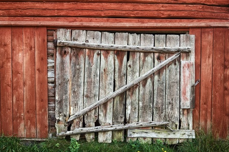 wooden facade: Wooden door on an old rustic red painted barn