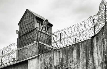 Guard tower and barbed wire on old prison wall  photo