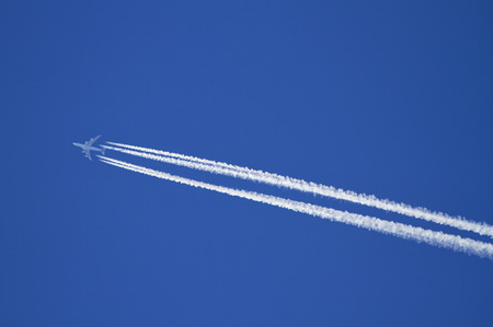 Airplane with condensation trails on a blue sky  photo
