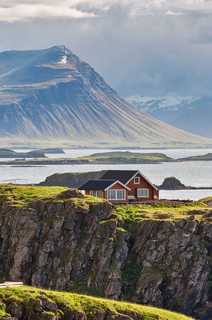 Idyllic red cottage with ocean view in Iceland. photo