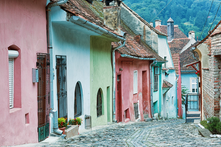 Old street with pastel coloured houses in Sighisoara, Romania.