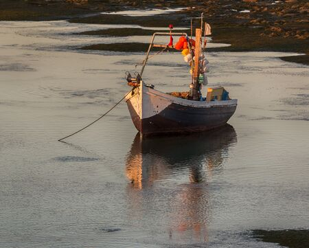 fishingboat: Old wooden fishingboat anchored at sunset. Stock Photo