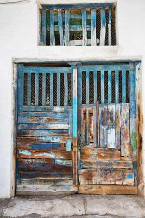Old dilapidated wooden door with peeled blue paint.