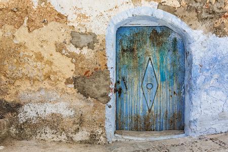 puertas antiguas: muro de piedra resistida y vieja puerta oxidada azul.