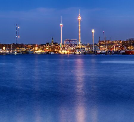 Illuminated towers at Stockholm waterfront at night.