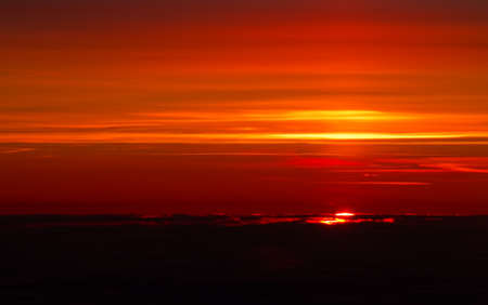 Sunset above the clouds in warm red colours.