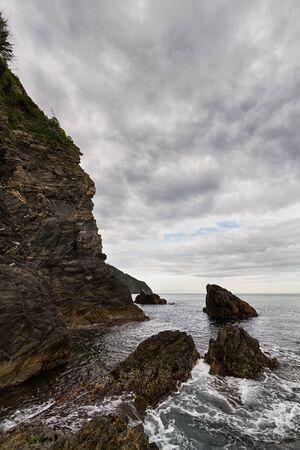 Rocky coastal area with cloudy sky.