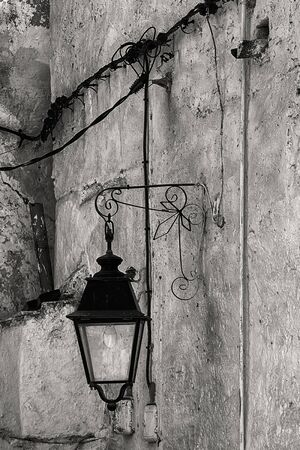 Old lantern in wrought iron, black and white image.