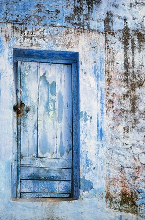 grungy: Blue grungy wooden door on dirty stone building. Stock Photo