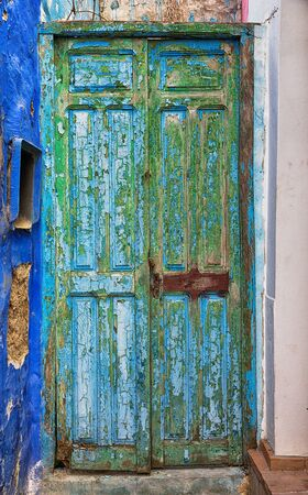 old doors: Old blue and green door with cracked paint. Stock Photo