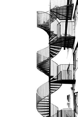 Metal spiral staircase for fire escape, black and white image. Stock Photo