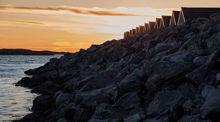breakwater: Coastal sunset and breakwater made of rocks.