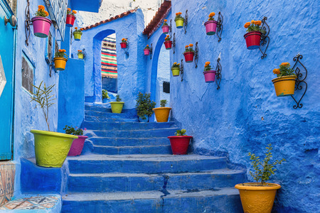 Blue wall and staircase decorated with colourful flowerpots. Stock Photo