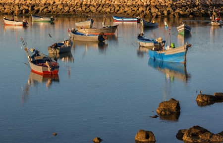 fishingboats: Old wooden fishing-boats in harbour at sunset.