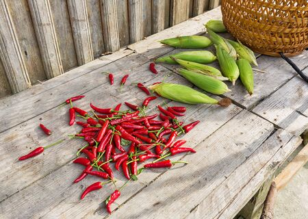 Fresh chili and corn on wooden table, food ingredients in rural China. Stock Photo
