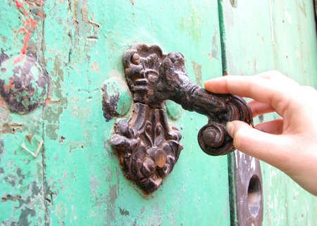 door handle: A woman knocking on the door of a house