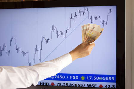stockbroker giving approval  with a euros in hand  fictitious market data  Stock Photo