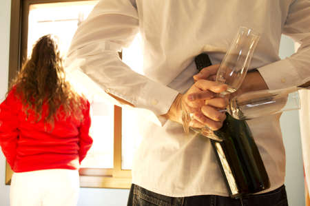 Man hiding champagne glasses and champage  and woman looking out the window Stock Photo