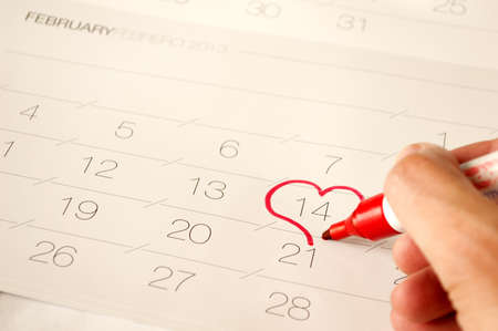 Man draw a heart shape in the calendar- february 14th in red