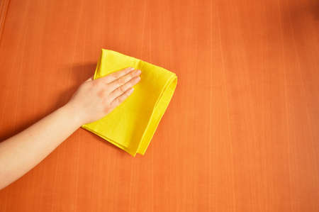 dusting: woman cleaning furniture  with yellow cloth Stock Photo