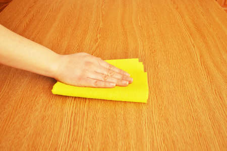 dusting: woman cleaning furniture table with yellow cloth Stock Photo