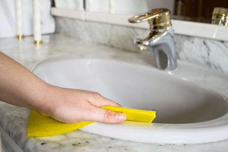 mujer limpiando: Una mujer limpia su cuarto de ba�o con tela amarilla