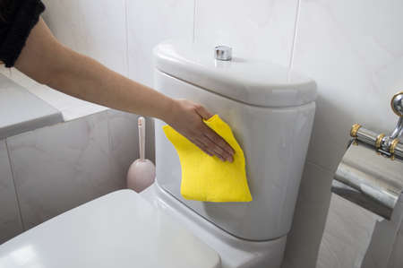 A woman cleans a toilet with yellow cloth photo