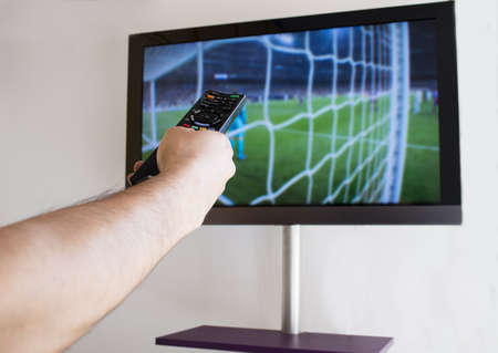 Hand holding TV remote control,Close-up, television showing soccer in the background  Stock Photo