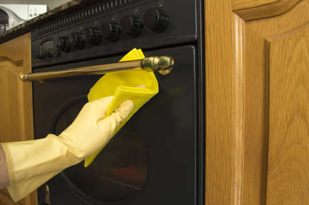 Female arms only cleaning the outside of an oven Stock Photo