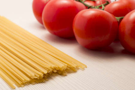 spaghetti and tomatoes on a table ready to cook photo
