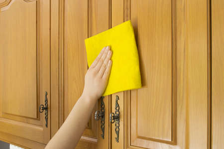Young woman in the Kitchen doing Housework cleaning cupboards