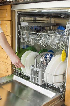 washup: Giovane donna in cucina fare i lavori domestici con la lavastoviglie