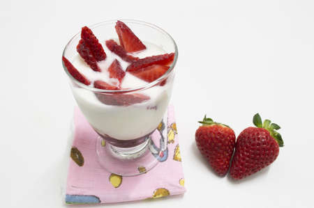 glass of yogurt with strawberries  isolated on white photo