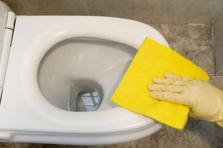 woman cleans a toilet with yellow cloth Stock Photo - 18930093