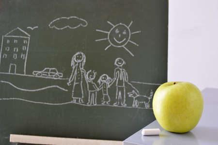 blackboard with a drawing of a boy and an apple to eat photo