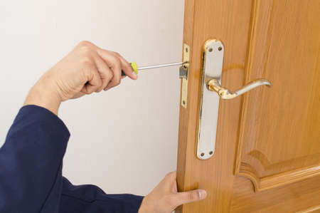 Carpenter fixing a lock in the door  with a screwdriver on close up Stock Photo