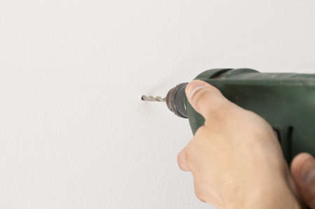 Closeup of a man drilling a hole in wall white and space copy photo